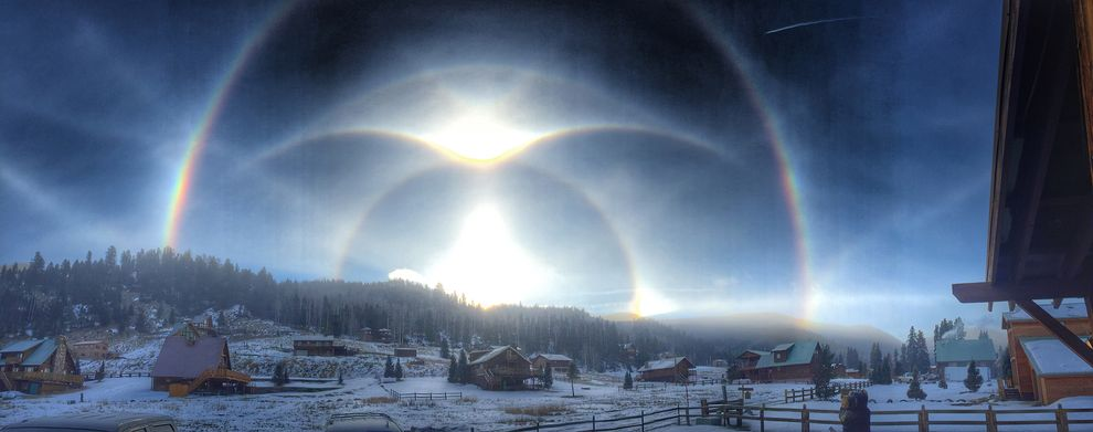 Ice halos arc over a snowy ridge in Red River, New Mexico. Photograph by Joshua Thomas