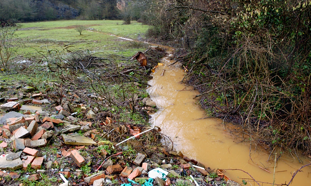 A discoloured stream running out of Brofiscin Quarry in south Wales. Toxic waste was dumped here in 1970s by contractors working for Monsanto. Photograph: Alamy