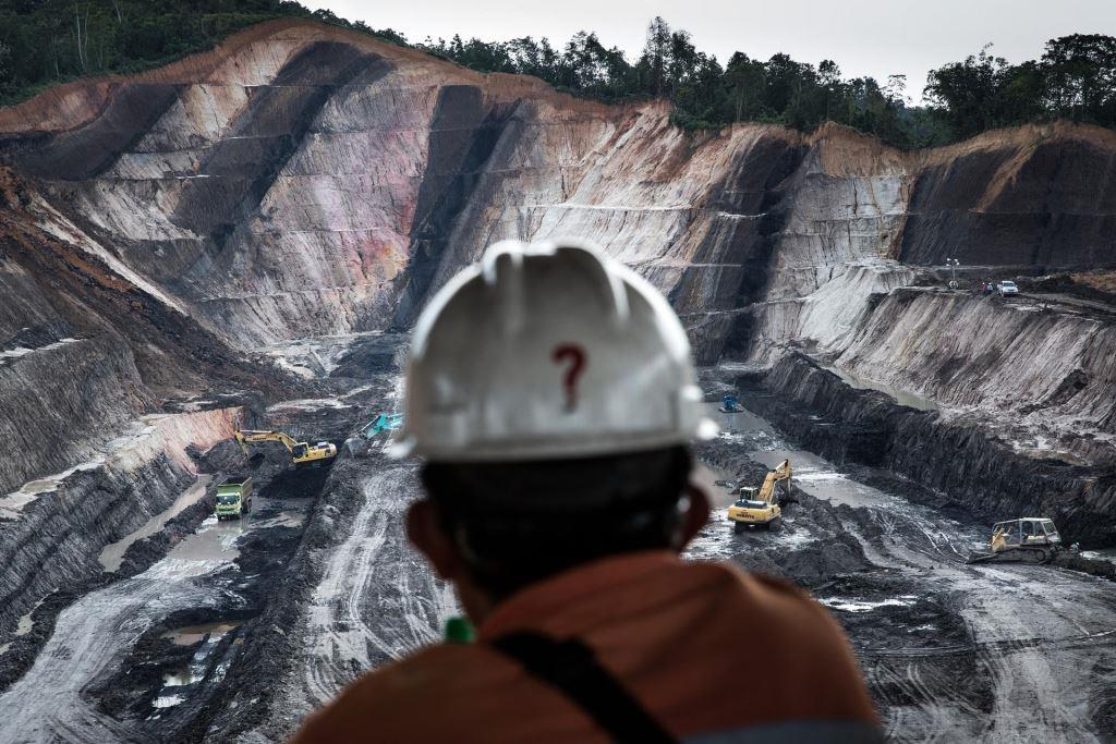 A worker on a break looks over an open-pit coal mine in Makroman, East Kalimantan, Indonesian Borneo. At its most destructive pattern of operation, coal extraction transforms mountain tops into giant holes using explosives, the cheapest way employed by many coal mining companies in Indonesia