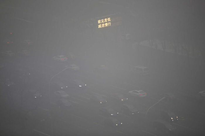 "Photo: Vehicles pass a road in Beijing as an electronic sign reads, ""low visibility, slow down"". (Reuters: Jason L)"