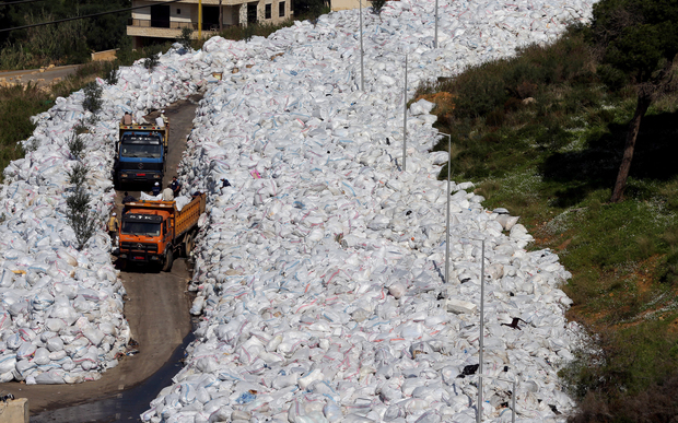 Rubbish trucks drive between a built-up pile of waste in Beirut on 25 February. Photo: AFP