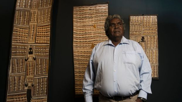 Djambawa Marawili with artworks by himself, his brother and his father. Photo: Louise Kennerley