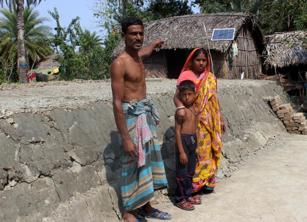 Kishore and Tripti Mondol and their son stand near the 4-foot-high clay platform the family recently built to try to keep their home above rising floodwaters in Joymoni, in Bangladesh's southwest Khulna district, February 24, 2018. Thomson Reuters Foundation/Manipadma Jena