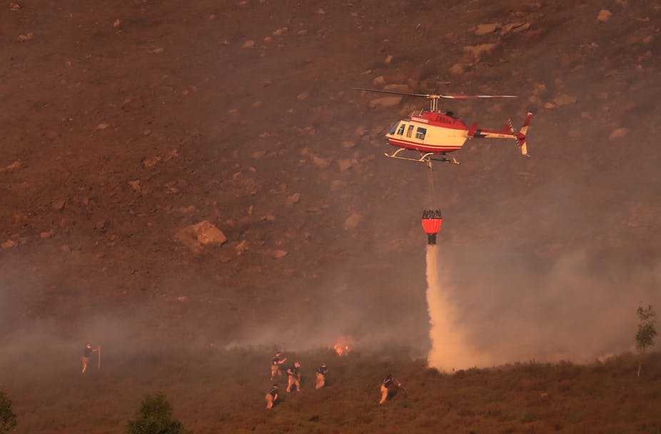 A helicopter drops water as firefighters tackle the wildfire on Saddleworth Moor, Greater Manchester. Peter Byrne/PA Wire/PA Images