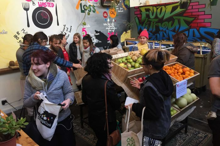 Photo: Shoppers check out food in the store, which opened on Sunday. (ABC News: James Oaten)