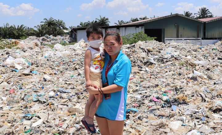 Koo Ze Quan (left) and Tan Siew Hoon stand on a mountain of plastic waste at an illegal factory in Jenjarom, Malaysia. Photo: RNZ / Nita Blake-Persen