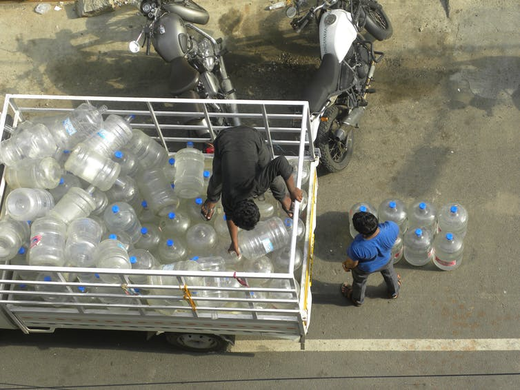 Men deliver water cans in Bangalore. Shutterstock